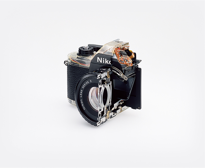 """Christopher Williams, """"Cutaway model Nikon EM. Shutter: / Electronically governed Seiko metal blade shutter vertical travel with speeds from 1/1000 to 1 second with a manual speed of 1/90th. / Meter: Center-weighted Silicon Photo Diode, ASA 25-1600 / EV2-18 (with ASA film and 1.8 lens) / Aperture Priority automatic exposure / Lens Mount: Nikon F mount, AI coupling (and later) only / Flash: Synchronization at 1/90 via hot shoe / Flash automation with Nikon SB-E or SB-10 flash units / Focusing: K type focusing screen, not user interchangeable, with 3mm diagonal split image rangefinder / Batteries: Two PX-76 or equivalent / Dimensions: 5.3 × 3.38 × 2.13 in. (135 × 86 × 54 mm), 16.2 oz (460g) / Photography by the Douglas M. Parker Studio, Glendale, California / September 9, 2007– September 13, 2007"""", 2008."""